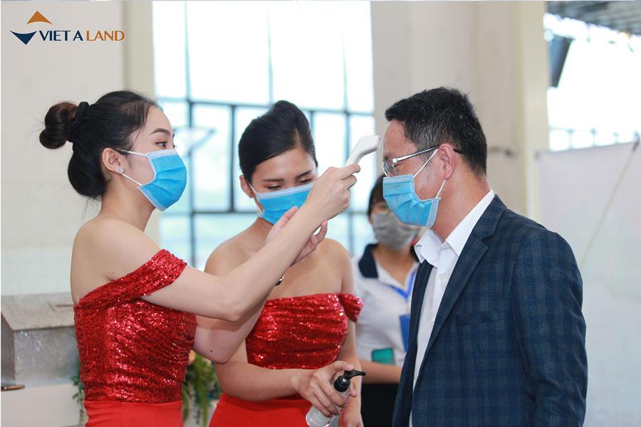 Nhân viên đo thân nhiệt và hỗ trợ khách hàng rửa tay bằng dung dịch xác khuẩn